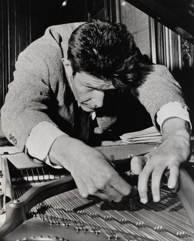 John Cage, afinando su piano o quizá poniendo algodones entre las cuerdas para que no rompa el fascinante silencio con molestas sonatas de Beethoven.