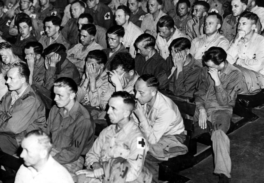 prisioneros de guerra alemanes viendo una película sobre los campos de concentración