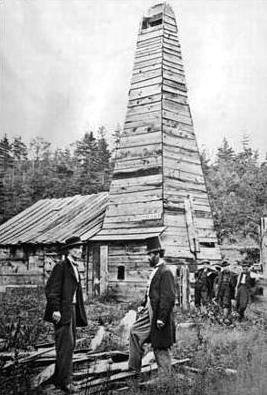 Edwind Drake posando junto al primer pozo de petróleo en Pensilvania