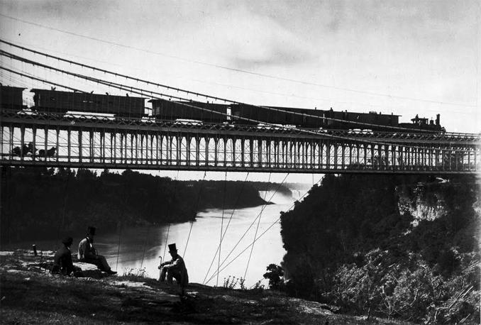 Puente sobre el Niágara, donde se aprecian los tirantes bajo el tablero. Locomotoras a vapor, carruajes, señores con bastón y chistera… el sabor del siglo XIX, en definitiva