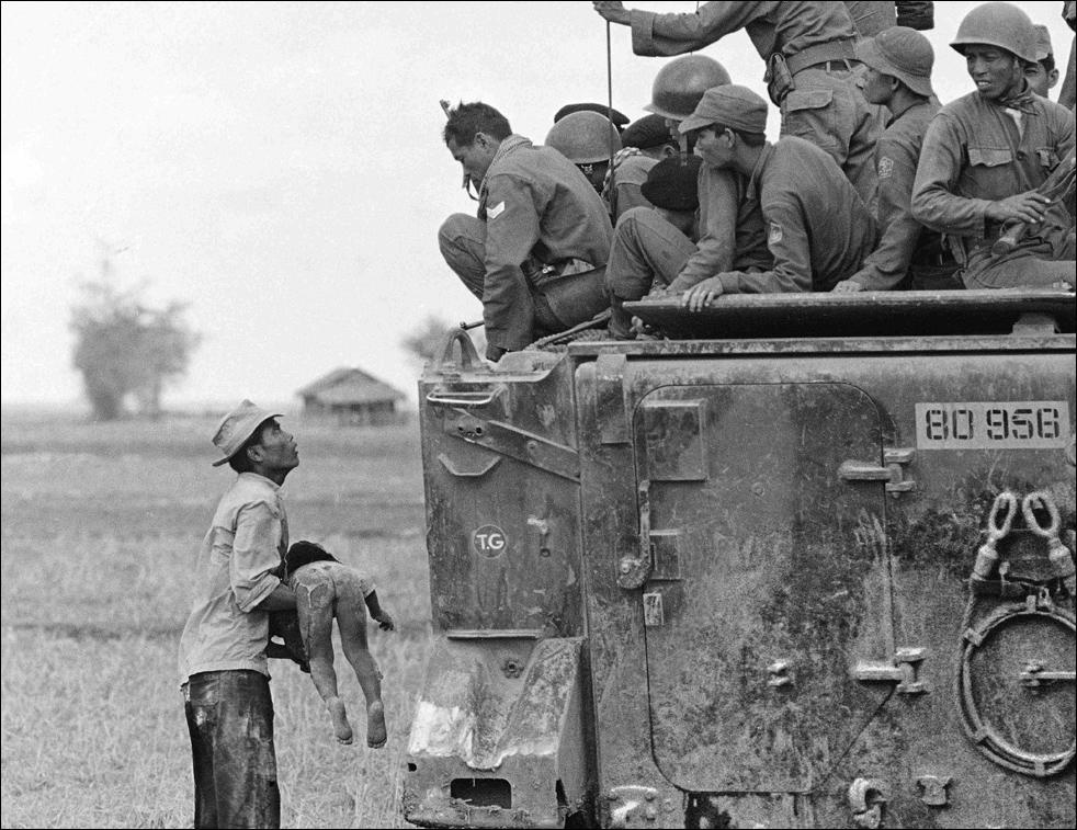 Un padre sostiene el cuerpo de su hijo frente a un blindado de tropas survienamitas - fotografía AP Horst Faas