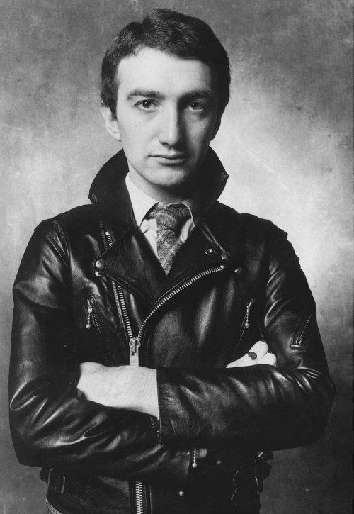 La combinación de chupa, corbata y peinado de oficinista aún no eran trendis cuando Deacon estaba en la escena.