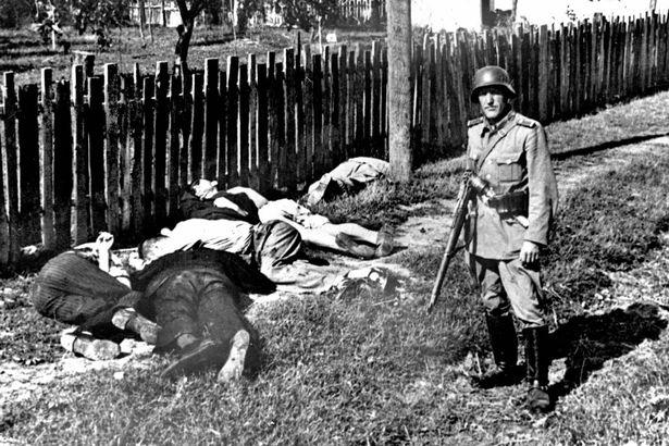 Soldado alemán posa junto a civiles yugoslavos muertos (PD).