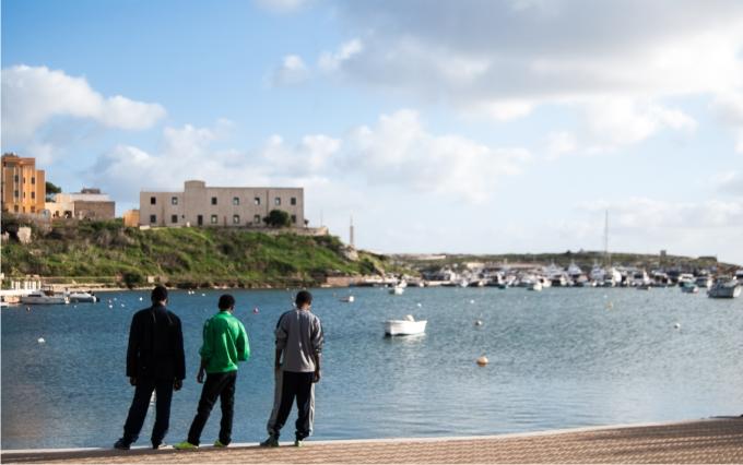 Migrantes eritreos contemplan las embarcaciones ancladas en la isla.