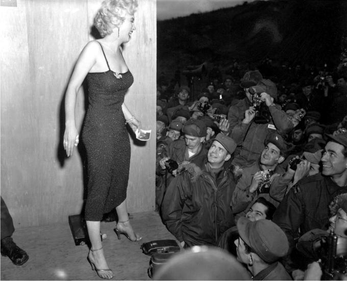 Marilyn Monroe posando para los fotógrafos después de una actuación en el área de la División de Infantería. EEUU, 17 febrero de 1954. (DP).