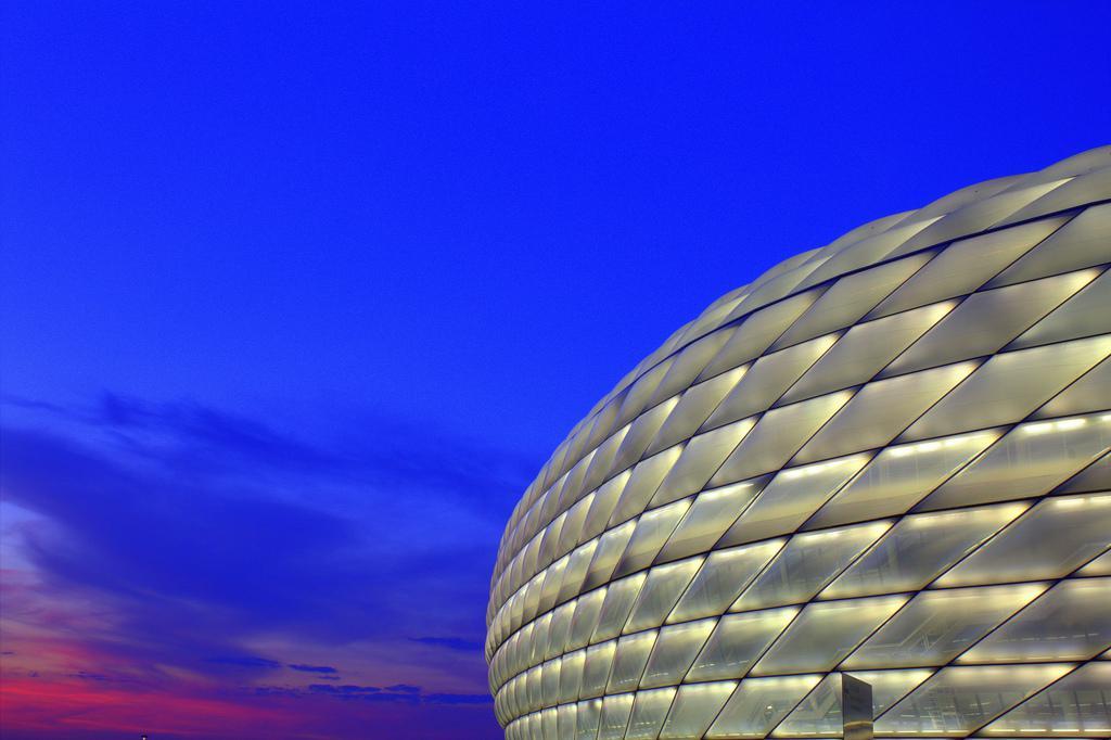 Rodeado de un cielo azul y rojo, el Allianz Arena de Munich se ilumina en blanco para un partido de la selección alemana de fútbol. Foto de Mohamed Yahya (CC)