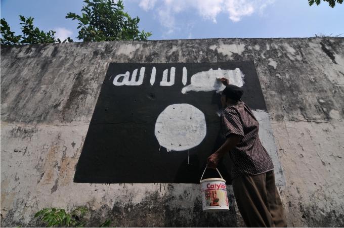 Un hombre tacha una ìntada de ISIS. Foto Cordon Press.