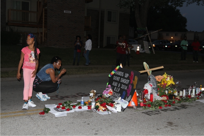 Una madre y su hija llevan llevan flores al lugar donde Michael Brown fue asesinado por la policía en Ferguson. Foto: Cordon Press.