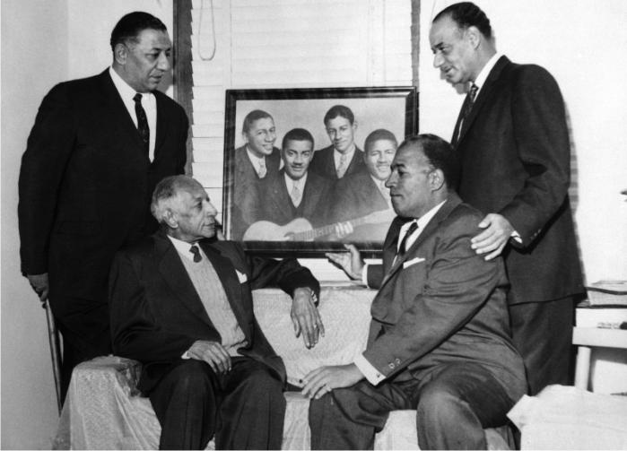 Los únicos e incomparables Mills Brothers, en la época en que cantaban junto a su padre, recordando con un cuadro sus años jóvenes y a su hermano difunto. (Foto: Corbis)
