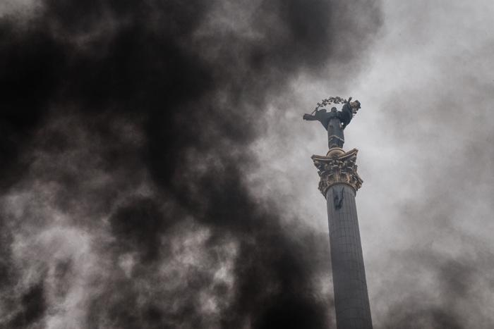 Estatua del Arcángel MIguel, que preside la Plaza de la Independencia de Kiev, entre humo, Magnífica fotografía de Mikhail Palinchak que simboliza a la perfección el caos ucraniano. (Foto: Corbis)