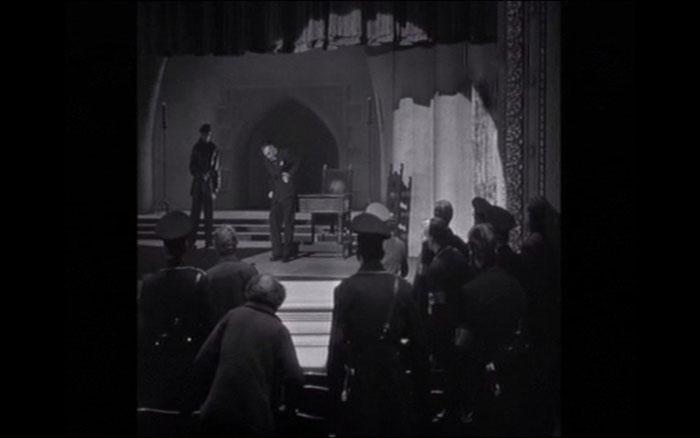 Funciones cruzadas del espacio: en la sala de interrogatorios de la escena anterior se representa para sobrevivir, y en el teatro no se representa, sino que se vive (y se muere).