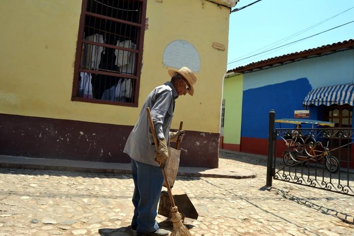 Un barrendero de avanzada edad en el centro de la ciudad de Trinidad.
