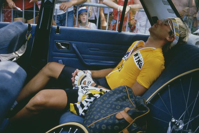 Laurent Fignon descansa en el coche de equipo ante la mirada curiosa de un niño del público (foto: Corbis)