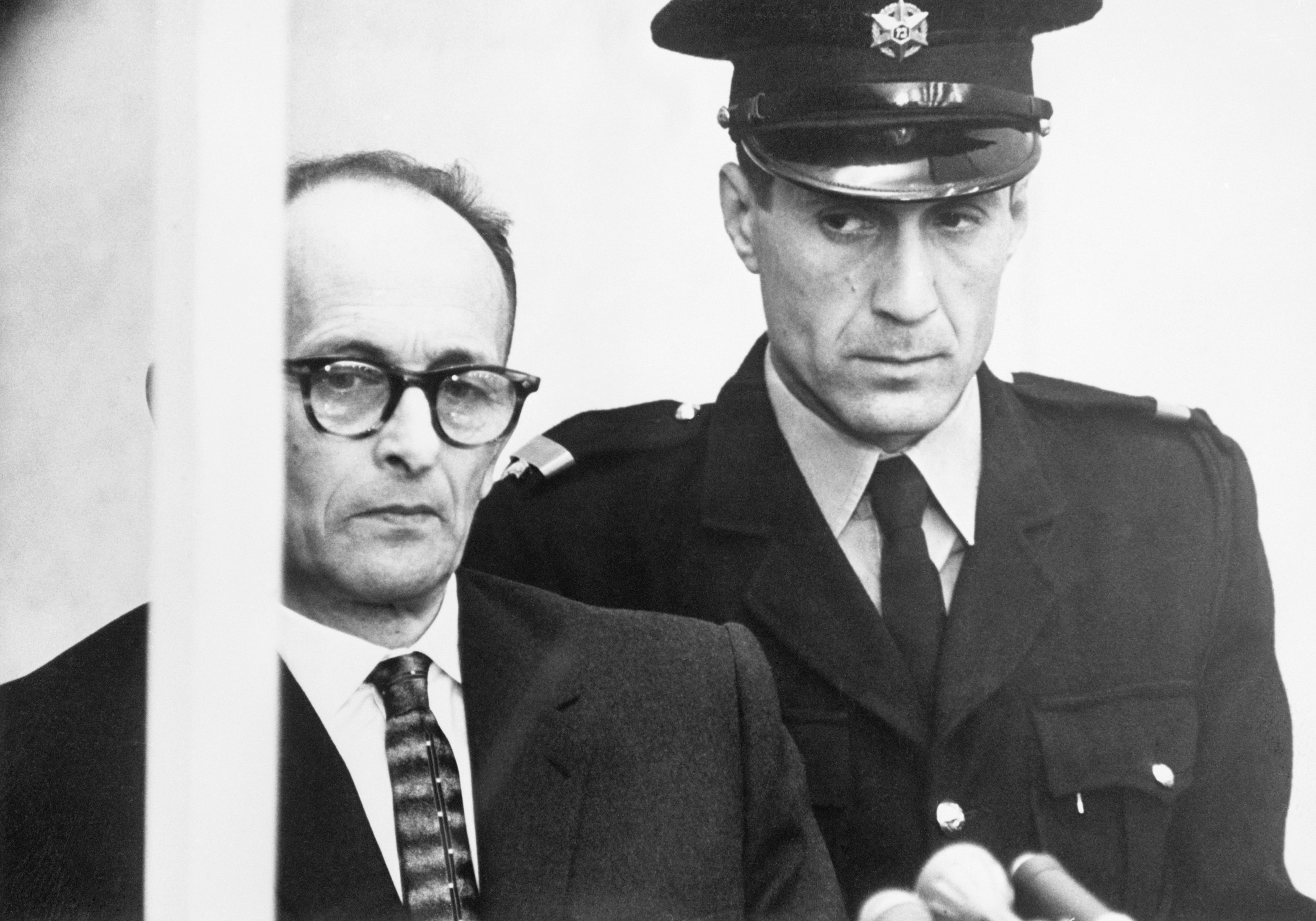 11 Apr 1961, Jerusalem, Israel --- Original caption: 4/11/1961-Jerusalem, Israel- A thin faced Adolf Eichmann listens to the reading of a 15 count indictment, accusing him of the murder of millions of Jews during World War II, as a guard stands beside him (R), April 11. The reading of the charges at the trial's opening took an hour and 15 minutes. --- Image by © Bettmann/CORBIS