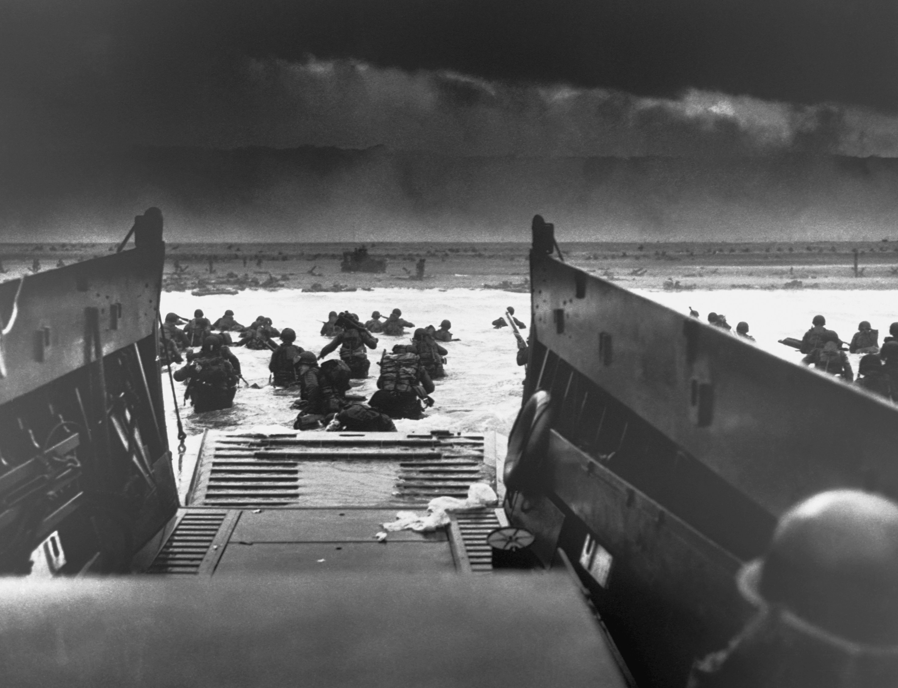 06 Jun 1944, France --- On D-Day, June 6, 1944, a landing craft just vacated by invasion troops points towards a fortified beach on the Normandy Coast. American soldiers wade to shore fighting heavy machine gun fire. --- Image by © CORBIS