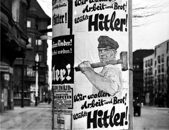 Cartel en una calle berlinesa en 1932, «Nosotros queremos trabajo y pan, vota por Hitler». Foto: Corbis.