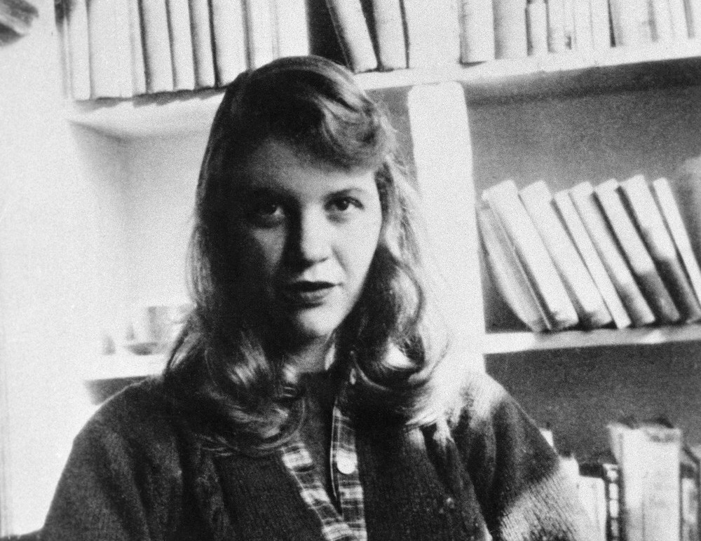 1950s-1963 --- Original caption: Photo shows author Sylvia Plath seated in front of a bookshelf. --- Image by © Bettmann/CORBIS