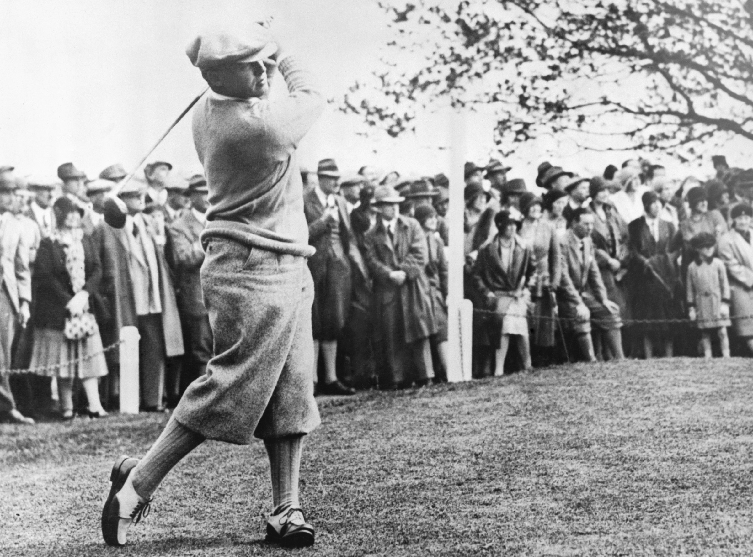 "ca. 1900s --- Original caption: Bobby Jones (b. 1902) American golfer and only player ever to make the ""Grand Slam"". Photograph full-length swinging golf club. --- Image by © Corbis"