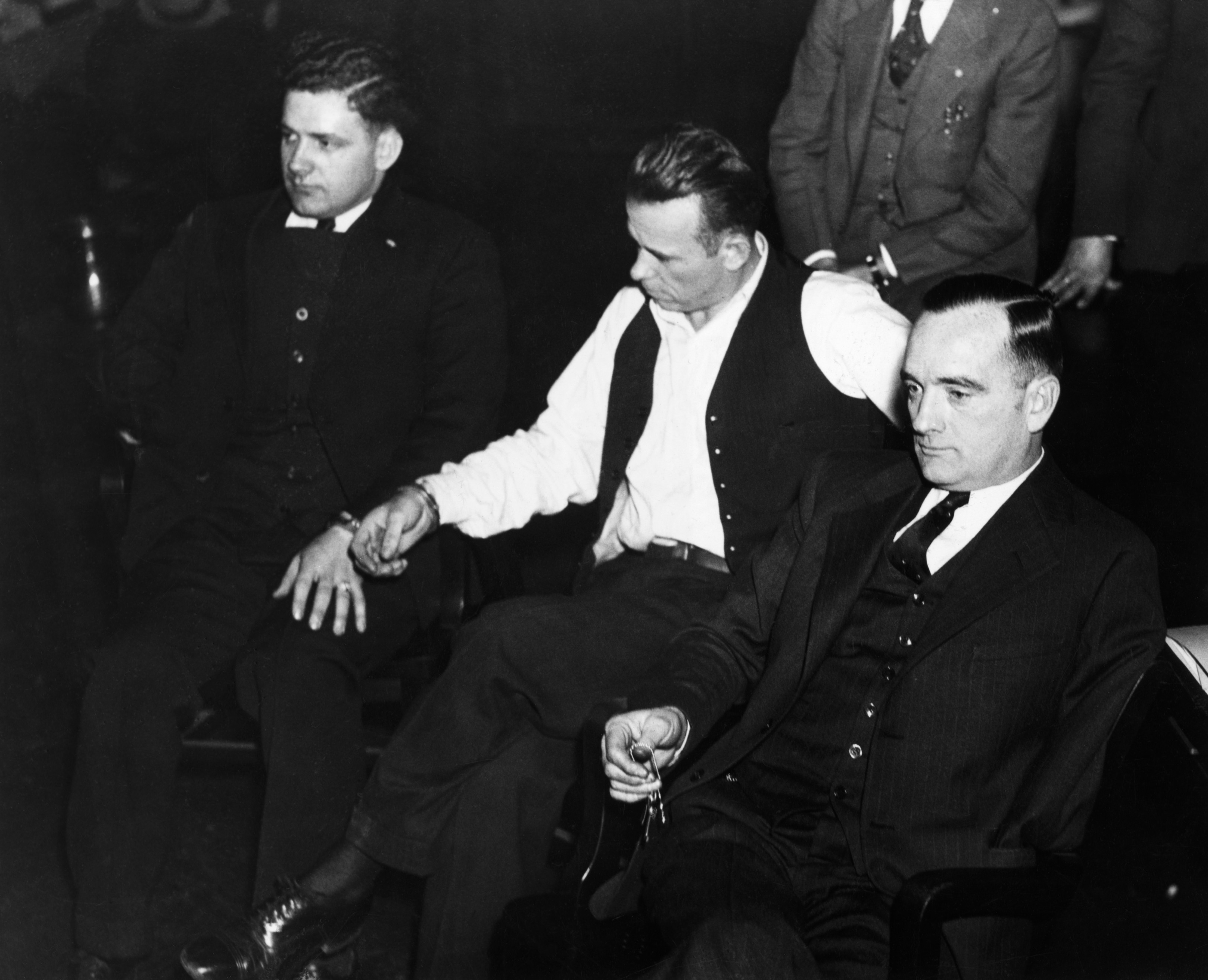 ca.1933, Indiana, USA --- Original caption: IN-John Dillinger, notorius criminal in Indiana court, manacled to Sheriff Holley. At right is attorney Joseph Ryan. Photograph. --- Image by © Corbis
