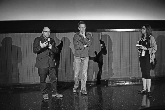 Andrew Feinstein (derecha), Johan Grimonprez (centro) y un batiburrillo de sombras (fondo) en la presentación de Shadow World.