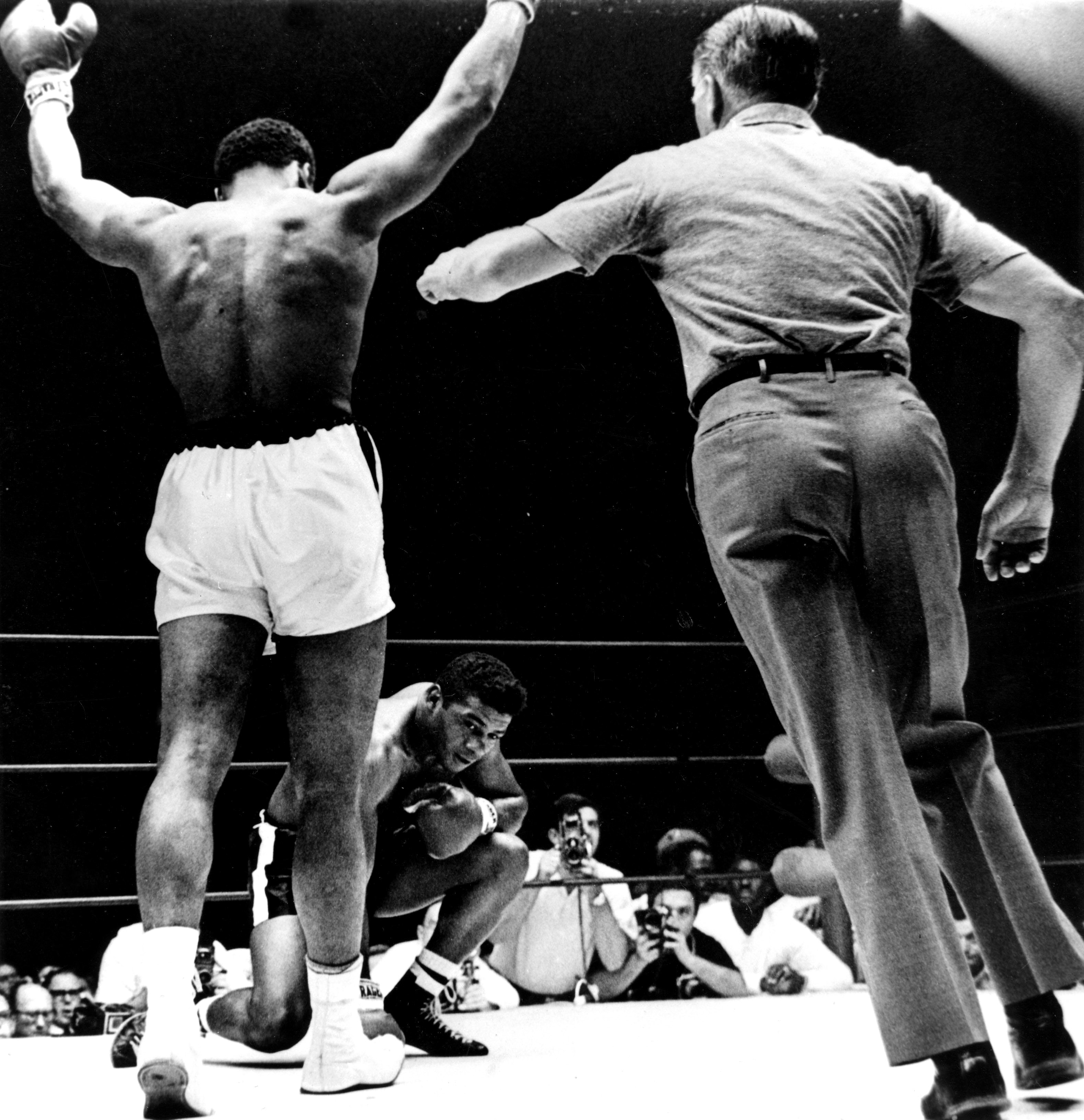 "Cassius Clay with arms raised, is waived to the neutral corner as Floyd Patterson (kneeling) takes a mandatory count of eight in the 6th round of their title fight in Las Vegas. Clay won on a technical knock-out in the 12th round to retain his title. The referee, Mr Krause, had to warn Clay for talking to Patterson early in the fight. ""Clay tried from the first round to humiliate Patterson"", Mr Krause said. ""He tortured him with remarks like, 'Come on American, come on white American'"". After the fight, Clay showered Patterson with unstinting praise and then typically demanded plenty of credit for himself from the ""American Public"". Clay spent nearly 15 minutes in the ring after the fight delivering a long impassioned oration, before finally heading for his dressing room. 22nd November 1965."