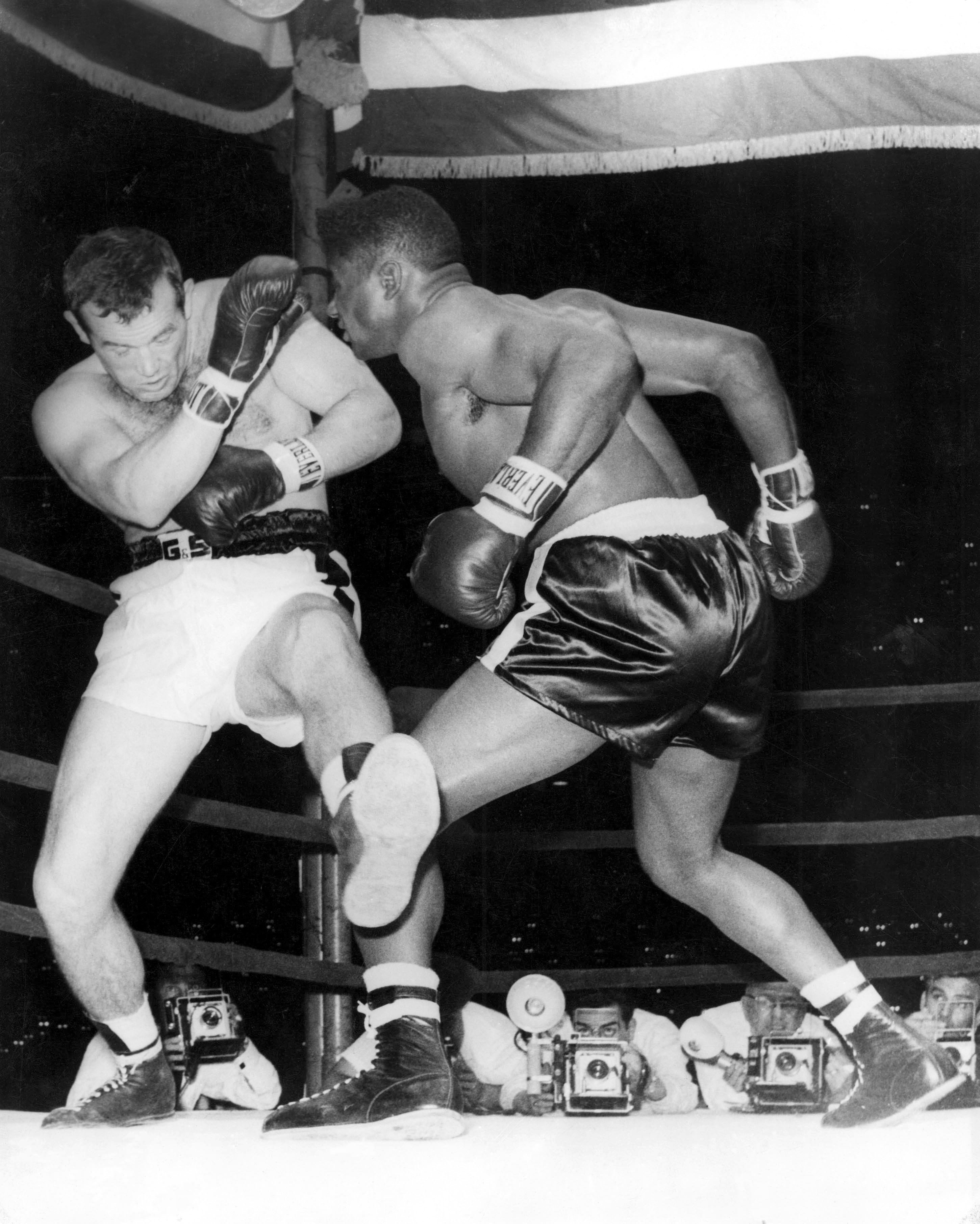 By knocking out world heavyweight boxing champion, Swedish Ingemar Johansson, in the fifth round of their title fight in New York, 25-year-old Floyd Patterson, made history as the only heavyweight champion of the world to regain his lost title. The fight was a complete reversal of the contest last June when Johansson, then the challenger, finished the fight and claimed the title in three rounds. Picture shows Johansson, forced against the ropes by Patterson's pushes, uses weird, unorthodox footwork, as he tries in vain to move away. 23rd June 1960