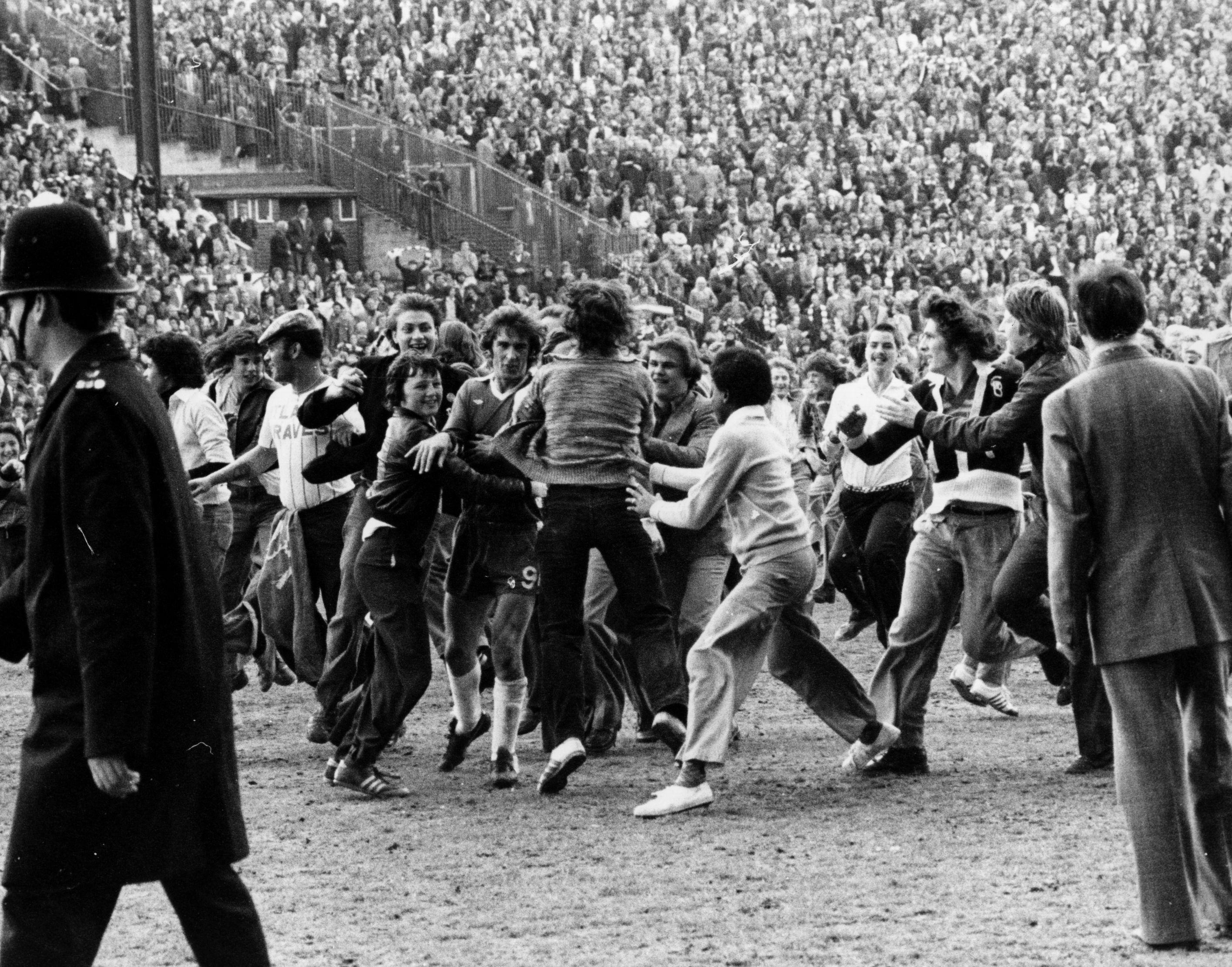 circa 1975: Sheffield United fans mob Steve Finneston as he tries to leave the football pitch. (Photo by Hulton Archive/Getty Images)