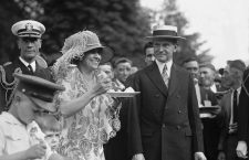 President Calvin Coolidge (1872-33) smiles along with his wife at a White House garden party in June 1926.