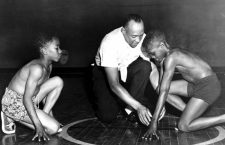 America's great Olympic track star Jesse Owens is showing two boys from the South Side Boys Club the starting position that brought him fame. Rajah Latimore (left) Sherman Davis 1st July 1954