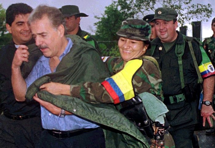 A rebel woman of the Revolutionary Armed Forces of Colombia (FARC), covers Colombian President Andres Pastrana from the rain before the start of a meeting in Los Pozos in Colombia's southern demilitarized zone, February 8, 2001. Pastrana met rebel leader Marulanda in an attempt to revive a stuttering two-year old peace drive. REUTERS/Guillermo Tapia-Ancol