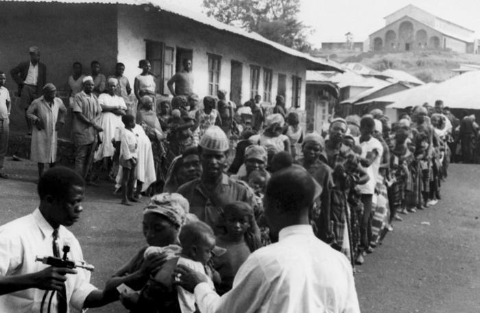 Captured in the tribal region of West Cameroon known as Banso, this historic photograph depicted the line of villagers awaiting their smallpox and measles vaccination during the country's participation in the Worldwide efforts to erradicate, and control these diseases during the 1960's.