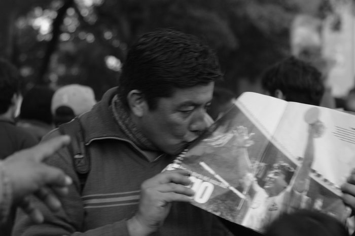 Buenos Aires, Argentina. 9th July 2014 -- An Argentine fan kisses a picture of Diego Maradona with the 1986 World Cup, during the semifinal against The Netherlands. -- Argentine football fans met in San Martin Square of Buenos Aires, to watch the FIFA World Cup semifinal against The Netherlands. Argentina defeated The Netherlands, and will go on to the World Cup Final.