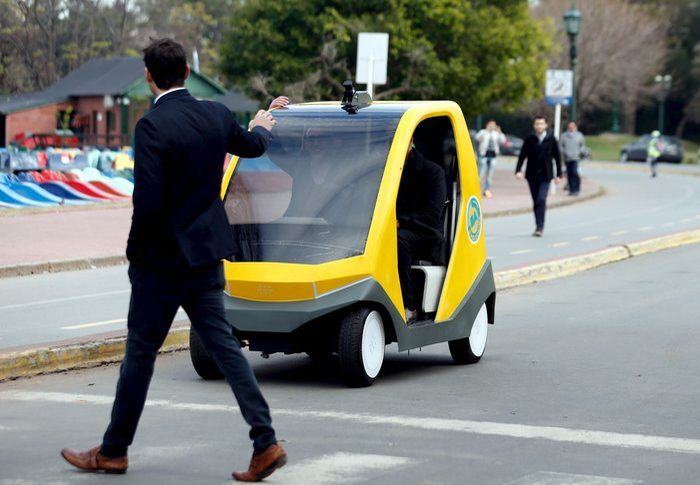 A man crosses the street as a prototype of an autonomous electric vehicle stops during its presentation in Buenos Aires, August 19, 2015. The autonomous vehicle, the first of its kind developed in Argentina, is able to fulfill the main functions of mobility of a traditional car but autonomously through the use of artificial intelligence that enables it to detect their surroundings and move without human intervention. REUTERS/Marcos BrindicciCODE: X90087