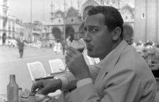 Italian actor Alberto Sordi, wearing a suit, portrayed while sipping a glass of tomato juice sitting on a terrace in St. Mark Square, salt, pepper and a lemon slice on the table in front of him, Venice, 1959. (Photo by Archivio Cameraphoto Epoche/Getty Images)