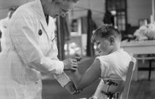 1947:  A hospitalised child suffering from polio shows off his biceps to a doctor.  (Photo by Keystone Features/Getty Images)