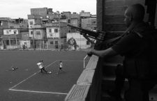 Boys play soccer as a policeman patrols one day after the occupation of the Mare slums complex in Rio de Janeiro, March 31, 2014. The federal troops and police occupied the Mare slums complex on Sunday to help quell a surge in violent crime following attacks by drug traffickers on police posts in three slums on the north side of the city, government officials said. Less than three months before Rio welcomes tens of thousands of foreign soccer fans for the World Cup, the attacks cast new doubts on government efforts to expel gangs from slums using a strong police presence. The city will host the Olympics in 2016.  REUTERS/Ricardo Moraes (BRAZIL - Tags: CRIME LAW SPORT SOCCER WORLD CUP)CODE: X02675