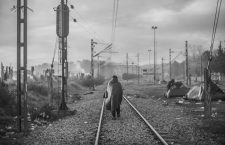 A refugee man walking on the train tracks during a cold stormy weather early morning in Eidomeni Refugee Camp. Macedonien/Greece, Eidomeni is now worldwide known for a sad reason. 12.500 refugees among them children, old women and men are stuck on the borders between Greece and Macedonien. They live in an open area next to the borders with only protection from rain and cold small tent.  *** Local Caption *** 19923223