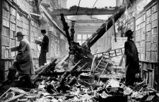 "HOLLAND HOUSE, Kensington, London. An interior view of the bombed library at Holland House with readers apparently choosing books regardless of the damage. Photographed in 1940. The House was heavily bombed during World War II and remained derelict until 1952 when parts of the remains were preserved..Holland House, originally known as Cope Castle, was a great house in Kensington in London, situated in what is now Holland Park. Created in 1605 in the Elizabethan or Jacobean style for the diplomat Sir Walter Cope, the building later passed to the powerful Rich family, then the Fox family, under whose ownership it became a noted gathering-place for Whigs in the 19th century. The house was largely destroyed by German firebombing during the Blitz in 1940; today only the east wing and some ruins of the ground floor still remain..In 1940, King George VI and Queen Elizabeth attended the last great ball held at the house. A few weeks later, on 7 September, the German bombing raids on London that would come to be known as the Blitz began. During the night of 27 September, Holland House was hit by twenty-two incendiary bombs during a ten-hour raid. The house was largely destroyed, with only the east wing, and, miraculously, almost all of the library remaining undamaged. Surviving volumes included the sixteenth-century Boxer Codex..Holland House was granted Grade I listed building status in 1949, under the auspices of the Town and Country Planning Act 1947; the Act sought to identify and preserve buildings of special historic importance, prompted by the damage caused by wartime bombing. The building remained a burned-out ruin until 1952, when its owner, Giles Fox-Strangways, 6th Earl of Ilchester, sold it to the London County Council (LCC). The remains of the building passed from the LCC to its successor, the Greater London Council (GLC) in 1965, and upon the dissolution of the GLC in 1986 to the Royal Borough of Kensington and Chelsea..Today, the remains of Holland House form a backdrop for the open air Holland Park Theatre, home of Opera Holland Park. The YHA (England and Wales) ""London Holland Park"" youth hostel is now located in the house. The Orangery is now an exhibition and function space, with the adjoining former Summer Ballroom now a restaurant, The Belvedere. The former ice house is now a gallery space. The grounds provide sporting facilities, including a cricket pitch, football pitch, and six tennis courts..In 1962, the Holland estate sold a piece of land immediately to the south of what is now the sports field for the construction of the Commonwealth Institute."