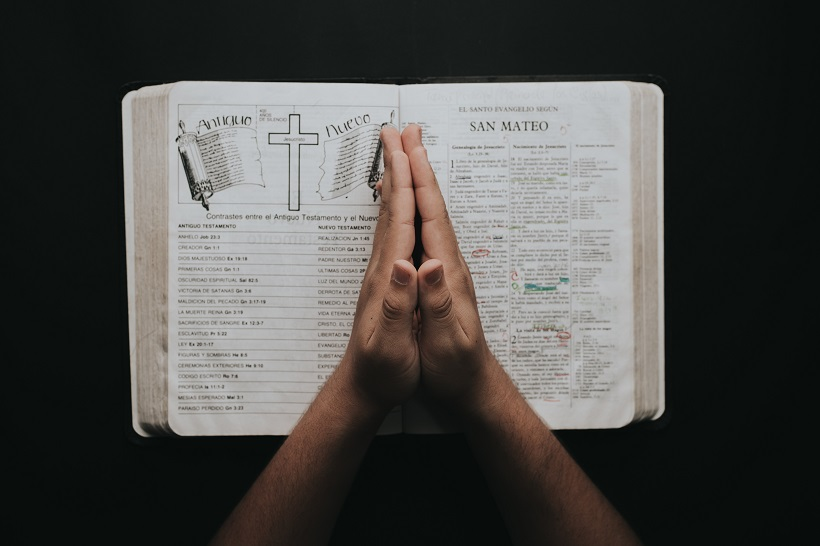 person placing hands on bible 2258251