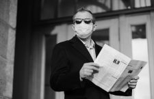 Caucasian man in sunglasses, medical mask and formal black suit, stands near building outdoor, holds newspaper in hands, poses at street, walks in quarantined city, finds out news from press