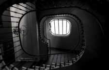 A greyscale shot of the spiral staircase of a building