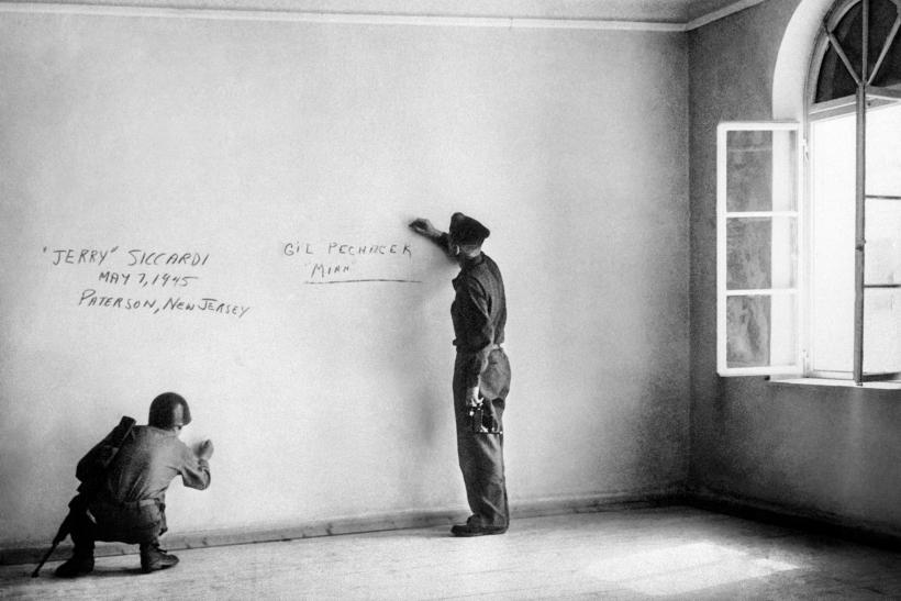 Dos soldados estadounidenses escriben grafitis sobre la pared de la habitación donde nació Adolf Hitler