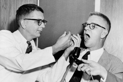 El doctor Harry L. Williams deposita chorros LSD desde una jeringa dentro de la boca de Carl Curt Pfeiffer